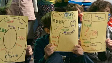 Elementary students holding signs with messages of hope