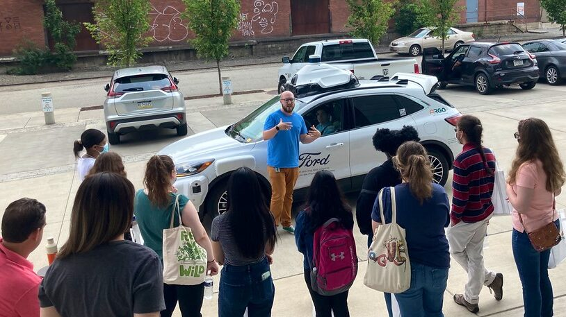 A group of students look at a self-driving vehicle